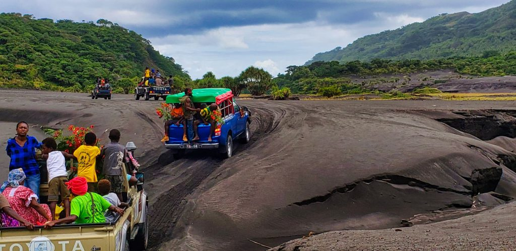 yasur volcano tanna vanuatu black volcanic ash driving pickups full of people
